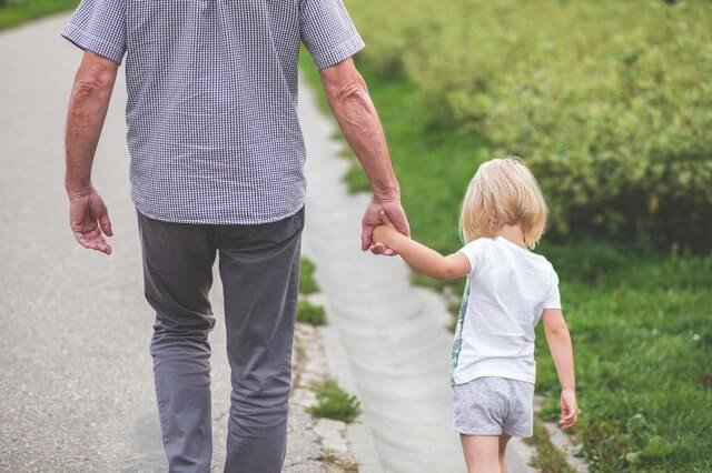 Grandfather holding granddaughter's hand